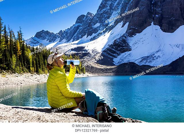 Female hiker drinking from water bottle on rocky alpine lake shoreline with snowed mountain cliffs in the background; Vermillion Crossing, British Columbia