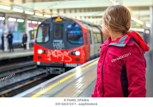 Little girl standing on the platform and watching the approaching overground train at the station in London, UK