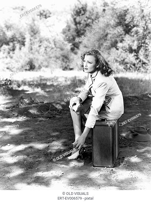 Young woman sitting on the side of the road on her suitcase, rubbing her aching feet All persons depicted are not longer living and no estate exists Supplier...