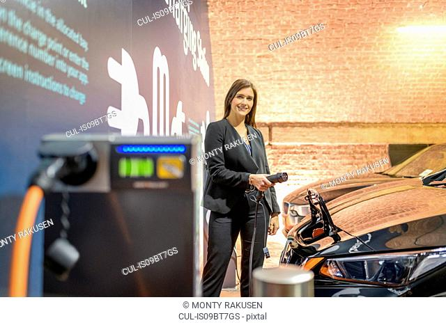 Portrait of businesswoman at electric vehicle charging station, Manchester, UK
