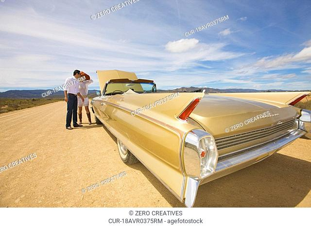 A couple, classic convertible, desert, middle on nowhere