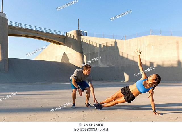 Male athlete helping friend with workout, Van Nuys, California, USA
