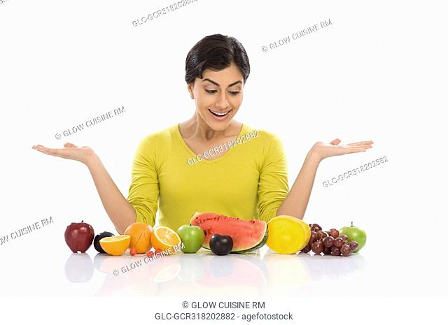 Woman looking at assorted fresh fruits and gesturing