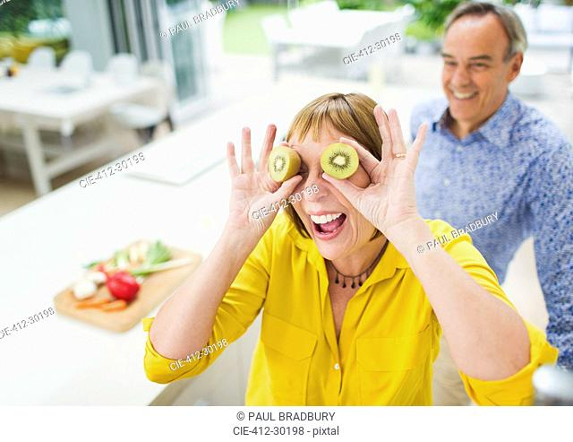 Portrait playful mature woman covering eyes with kiwi slices