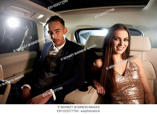 Attractive young couple in the back of a limo look to camera