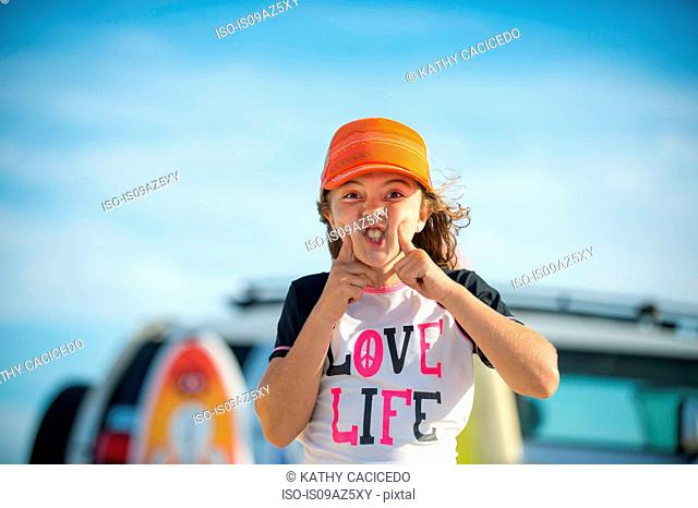 Portrait of young girl at beach, pulling funny face