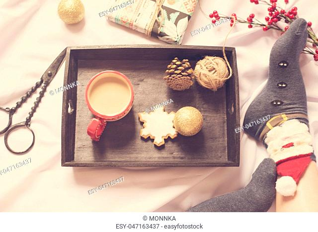 Cute photo of woman's feet with Christmas socks. Girl with presents sitting on a bed. Holiday morning with gifts. A tray with cocoa, ginger snowflake biscuit
