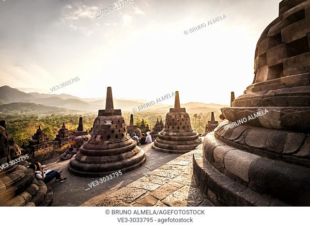 Asian tourists enjoying sunset over unroofed pyramid of Borobudur Temple, crowned by bell-shaped stone domes (Magelang Regency, Central Java, Indonesia)