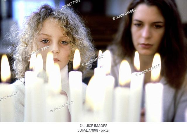Closeup of candles lit with woman and child praying in church