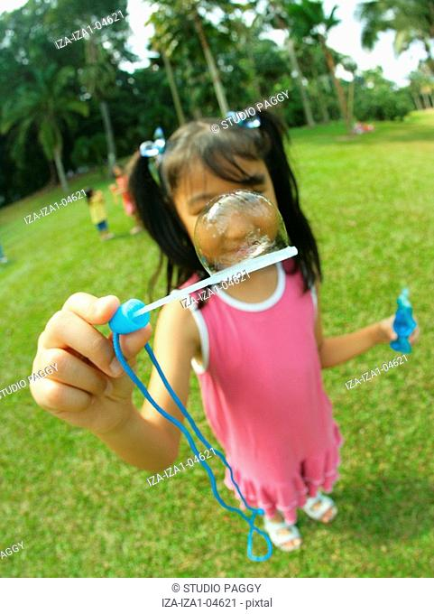 Close-up of a girl holding a bubble wand