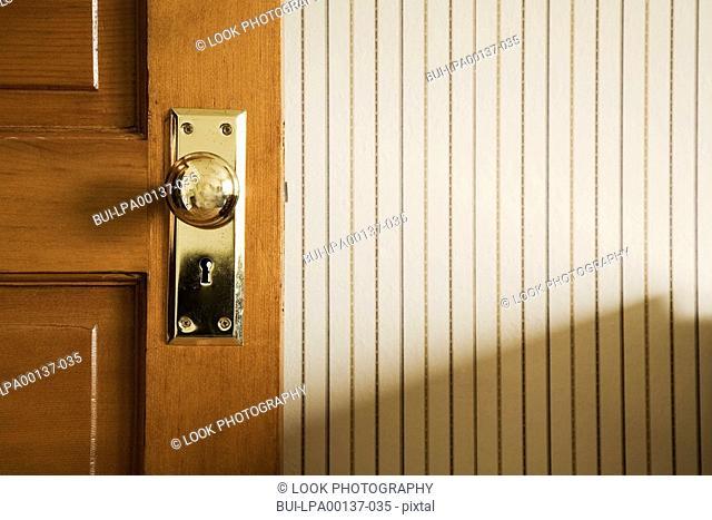 Close up of an open door with brass lock and door knob