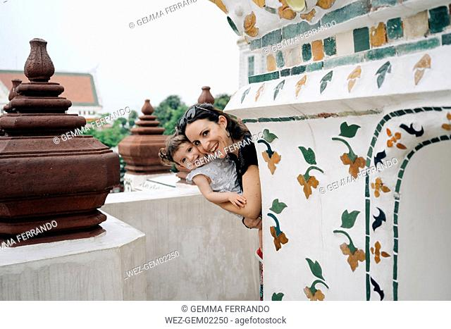 Thailand, Bangkok, Wat Arun, Portrait of happy mother and daughter visiting the Buddhist temple