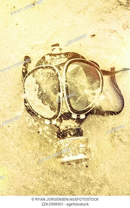 Retro stylised gas mask covered in sand during a gale force conflict. Operation desert storm