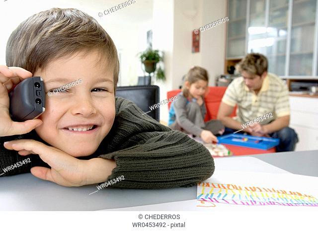 Portrait of a boy talking on a cordless phone