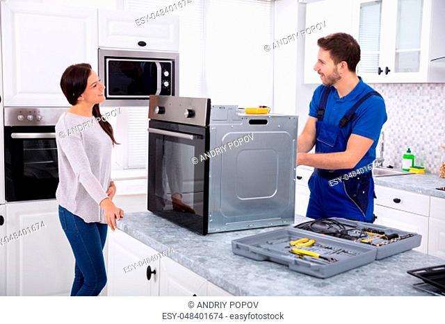 Smiling Repairman Repairing Oven On Kitchen Worktop In Front Of Woman