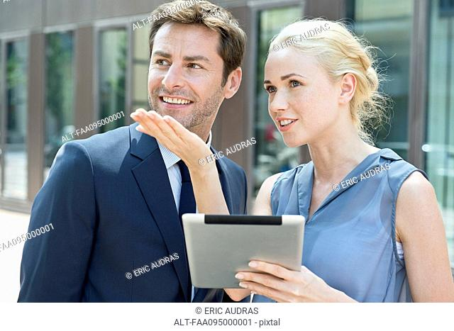 Real estate agent with digital tablet showing property to potential buyer