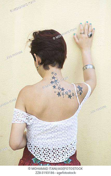 Rear view of a stressed woman hand touching wall
