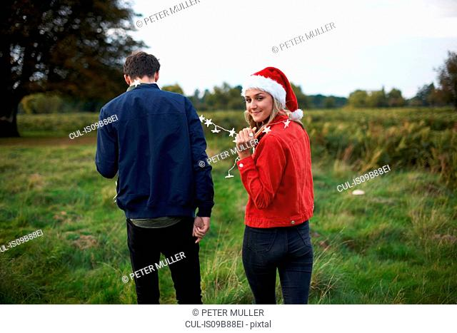 Rear view of young couple in santa hat and xmas light garland strolling in field