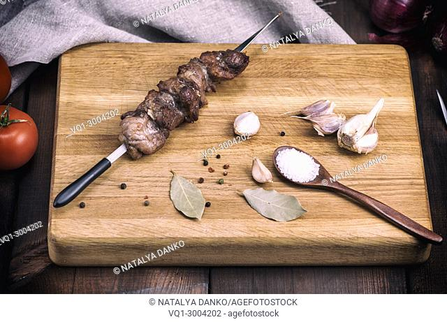 fried pieces of pork on a skewer lie on a kitchen board, wine tinting