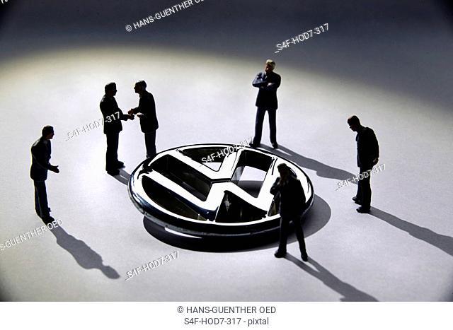 Modellfiguren stehen um VW-Logo herum