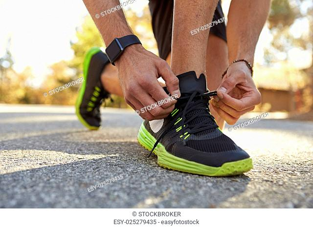 Male runner squatting in road tying his sports shoe close up