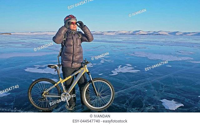 Man and his bicycle on ice. He stand and looks at the beautiful sunset. The cyclist is dressed in a gray down jacket, backpack and helmet