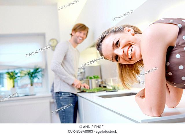 Woman turning to look over shoulder, man preparing food in background