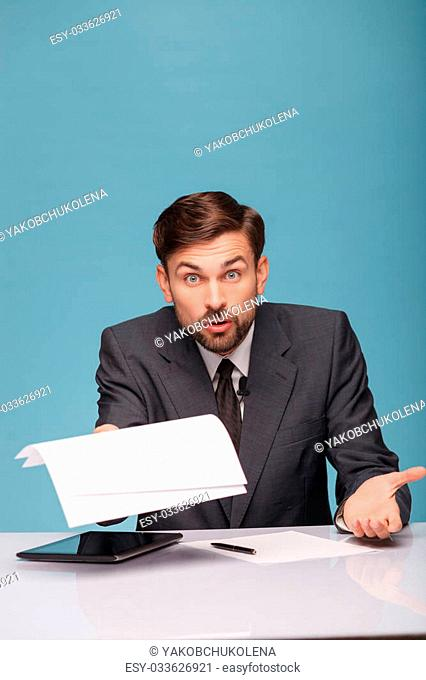 Cheerful male tv reporter is looking at camera with shock. He is holding papers and raising in with question. The man is sitting at a desk near the tablet