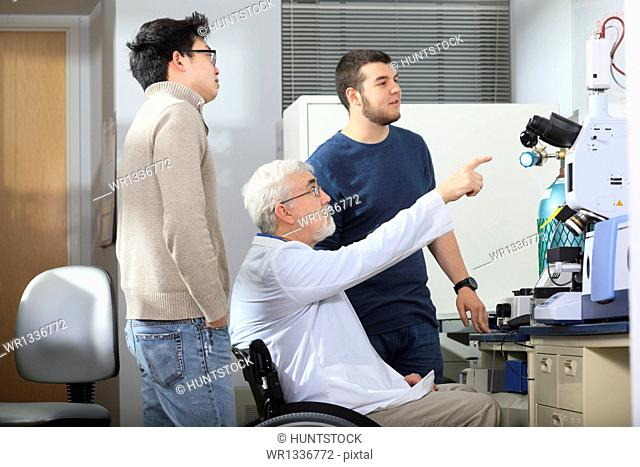Professor with muscular dystrophy working with engineering students looking at x-ray fluorescence analyzer in a laboratory