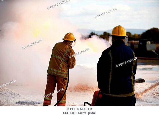 Firemen training, firemen spraying firefighting foam at training facility