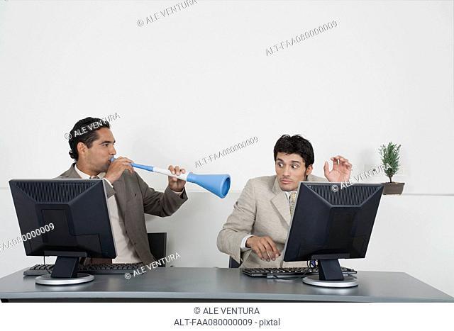 Businessman blowing vuvuzela horn into colleague's ear