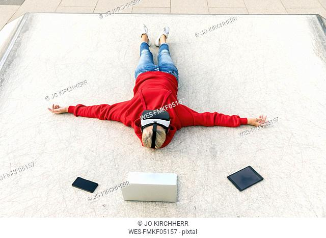 Senior woman lying on the ground wearing VR glasses next to mobile devices