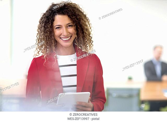 Portrait of smiling businesswoman with tablet in office