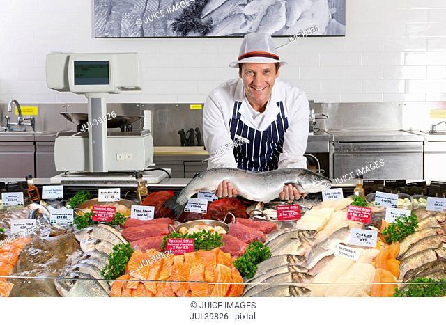 Fishmonger In Fresh Fish Department Of Supermarket