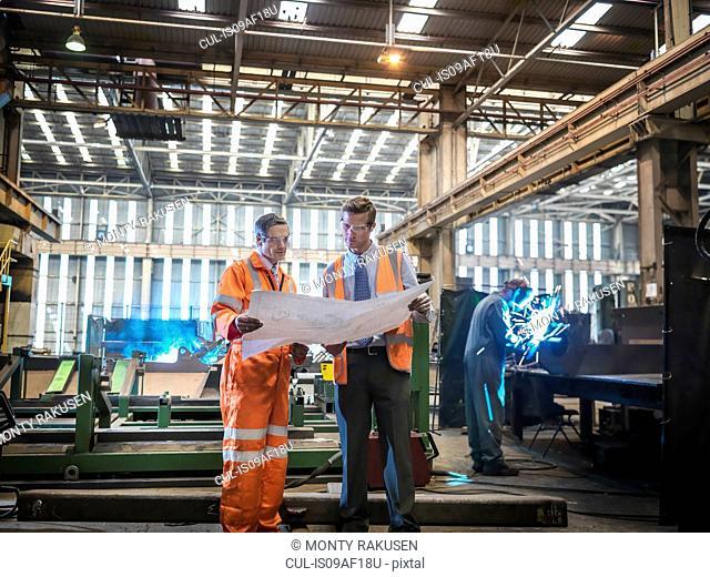 Engineers inspecting engineering drawings in factory