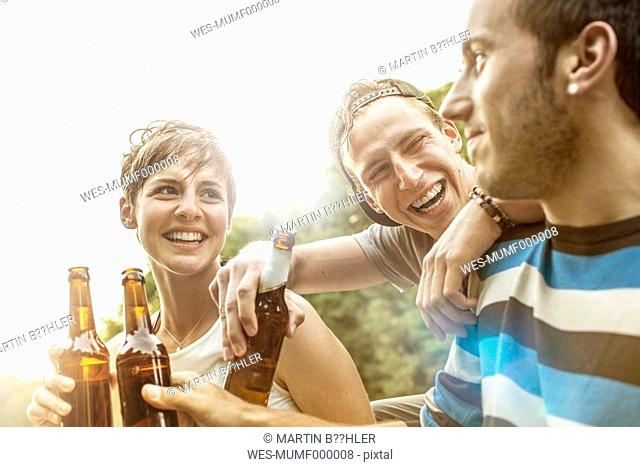 Three frinds relaxing with bottles of beer