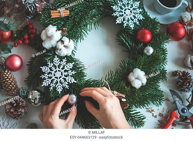 Florist's Hands with Christmas Tree Twig, Snowflakes, Glass Balls and Cotton Flowers