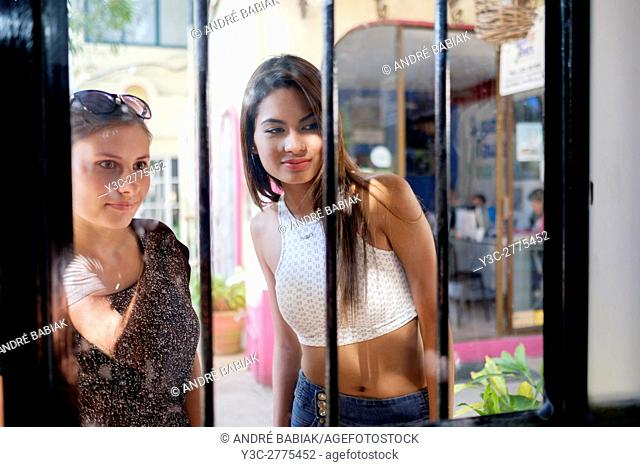 Two young women looking into a store from outside. Shopping, Puerto Vallarta, Mexico