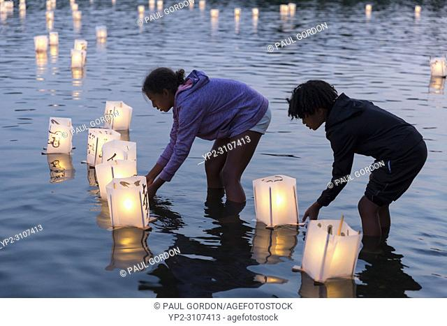 Seattle, Washington: A young girl and boy place paper lanterns in the lake at the From Hiroshima To Hope gathering at Green Lake Park
