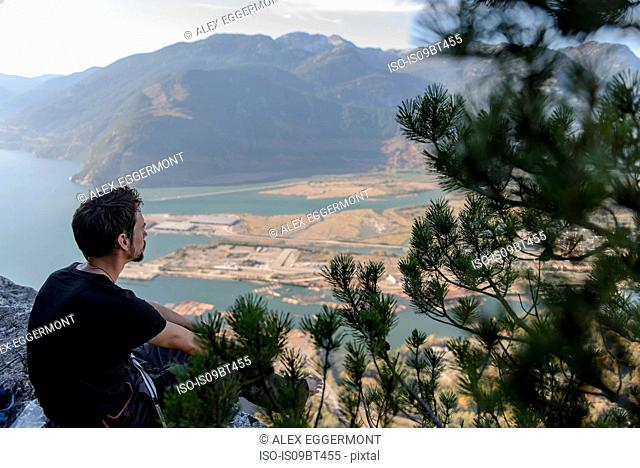 Male rock climber looking out over lake from The Chief, Squamish, British Columbia, Canada