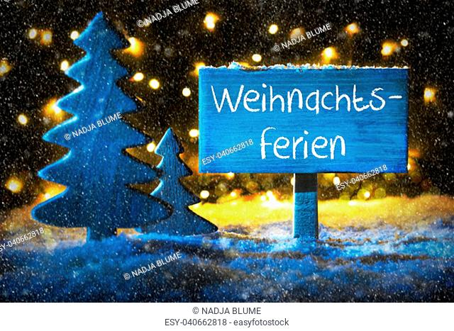 Sign With German Text Weihnachtsferien Means Christmas Holidays. Blue Christmas Tree With Snow And Magic Glowing Lights In Backround And Snowflakes