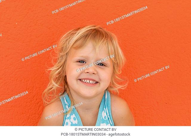 Portrait of a four year old girl against an orange wall