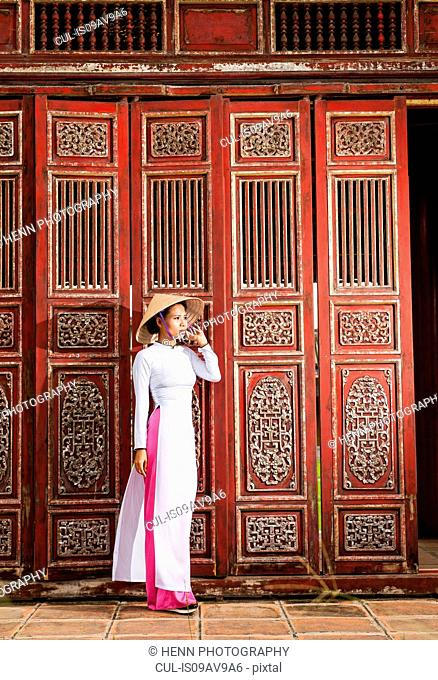 Full length view of mid adult woman wearing ao dai dress and conical hat standing in front of ornate wooden doors looking away, Hue, Vietnam