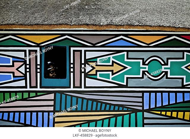 Woman of the Ndebele tribe looking out of a window of her house with traditional facade paintings, South Africa, Africa