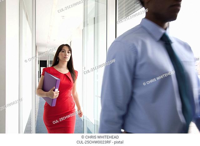 Two business people walking past camera