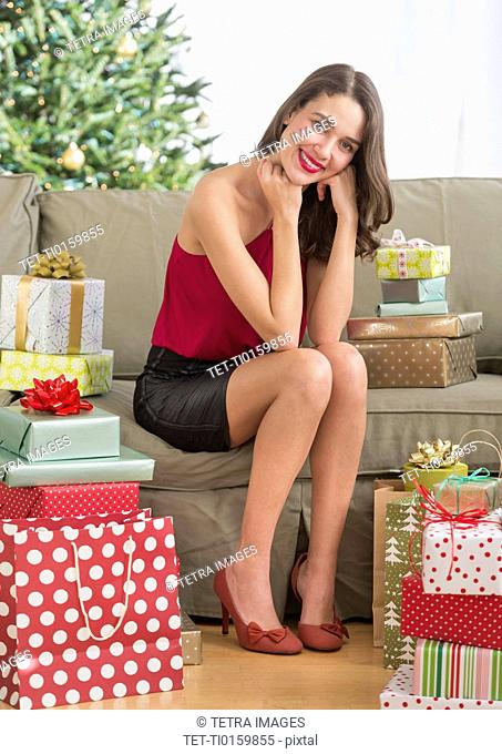 Woman surrounded with christmas gifts sitting on sofa