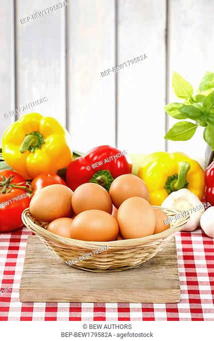 Pile of eggs, fresh vegetables in the background