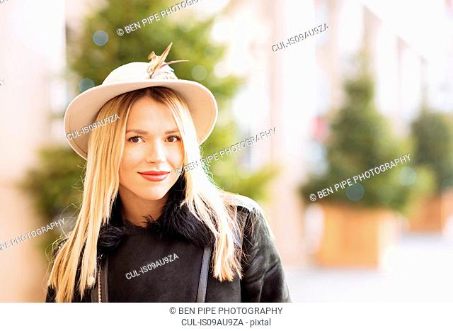 Portrait of stylish young woman wearing felt hat, Covent Garden, London, UK
