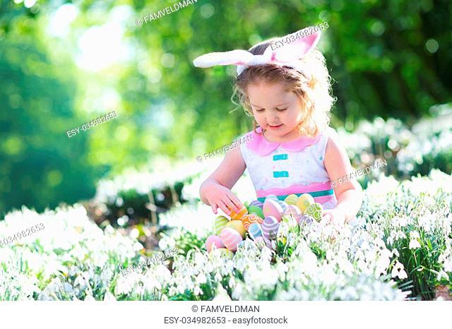 Little girl having fun on Easter egg hunt. Kids in bunny ears and rabbit costume. Children searching for eggs in the garden