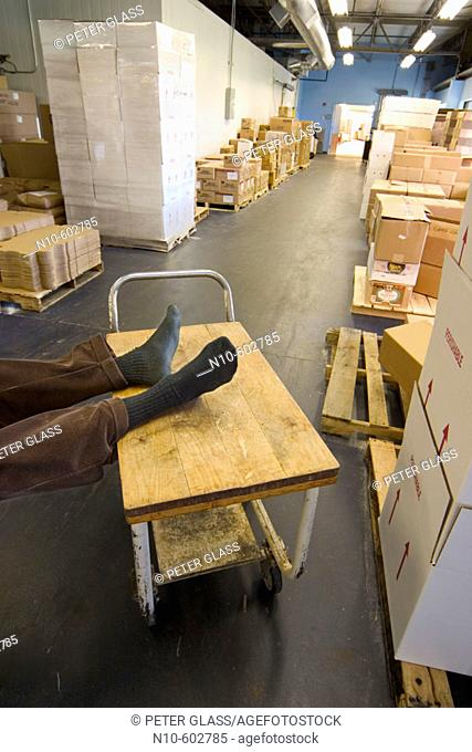 Man's feet, wearing just socks, resting on a rolling cart in a factory's storage area
